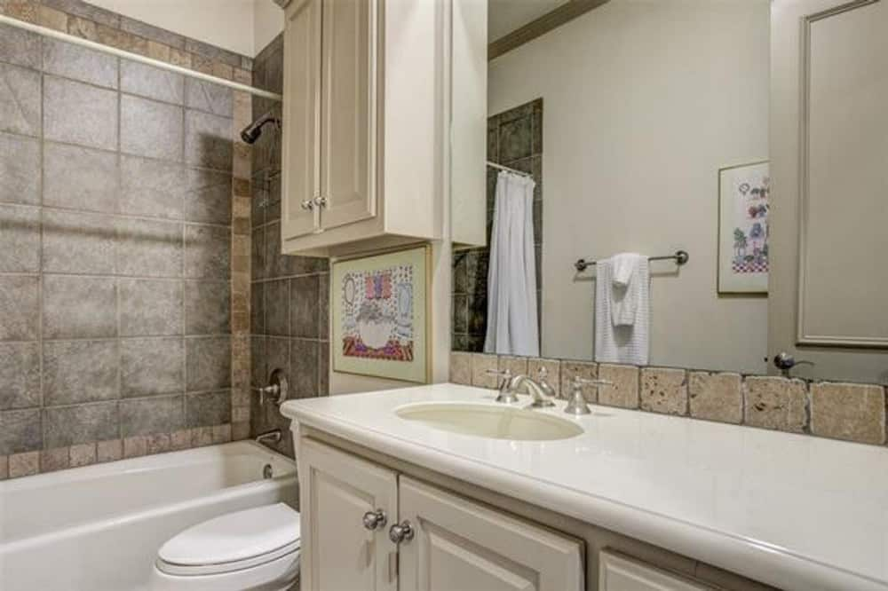 Bathroom with white vanity, a toilet, and a tub and shower combo.
