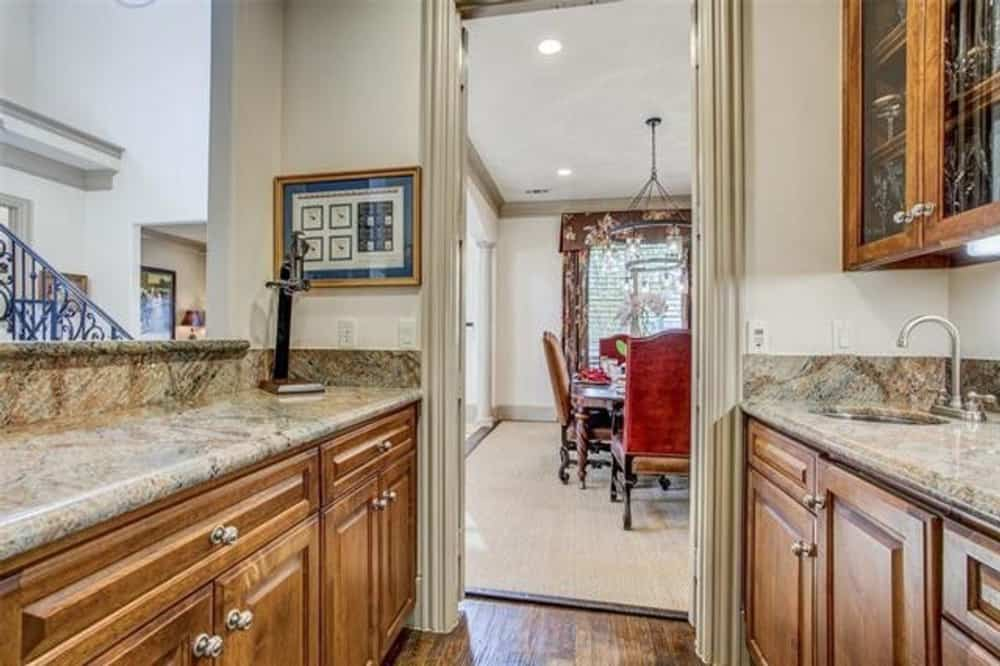 The kitchen opens into the formal dining room with a large area rug and a louvered window.