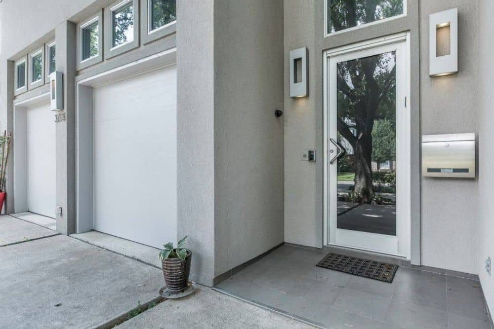 Home entry with a glazed entry door flanked by modern sconces.