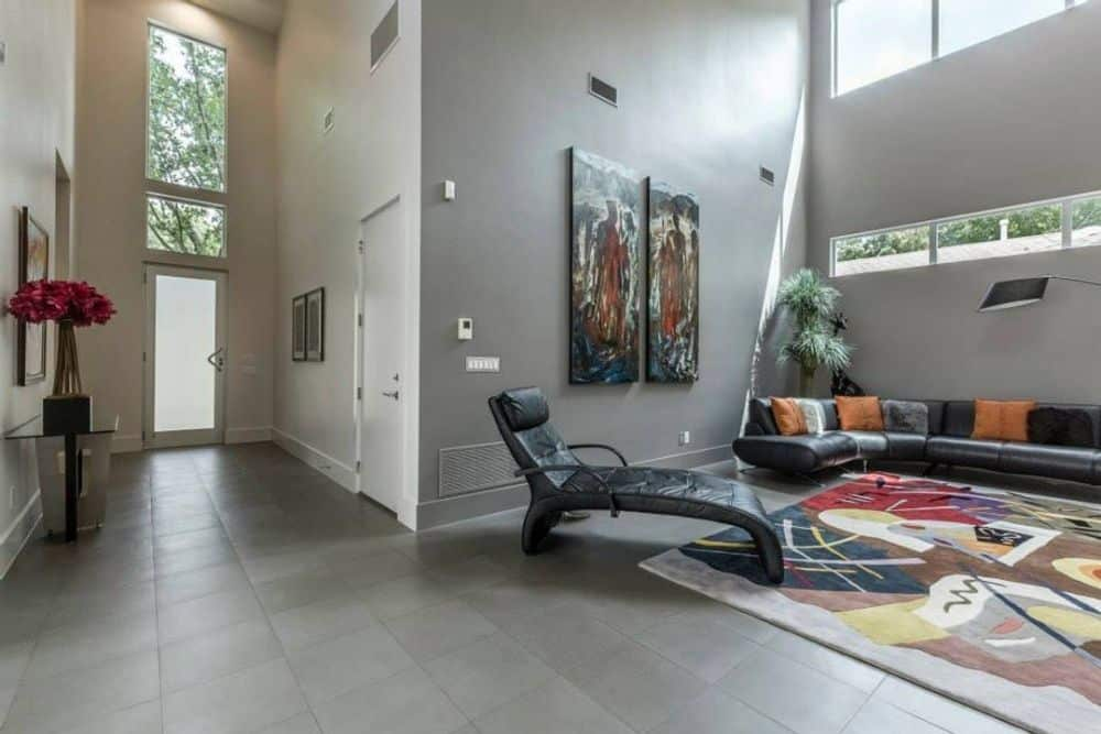 Tall transom windows bring natural light to the foyer. It opens into the living room complete with a leather sectional and a contemporary chaise lounge.