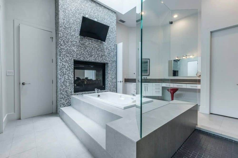 Primary bathroom with a deep soaking tub warmed by a double-sided fireplace.
