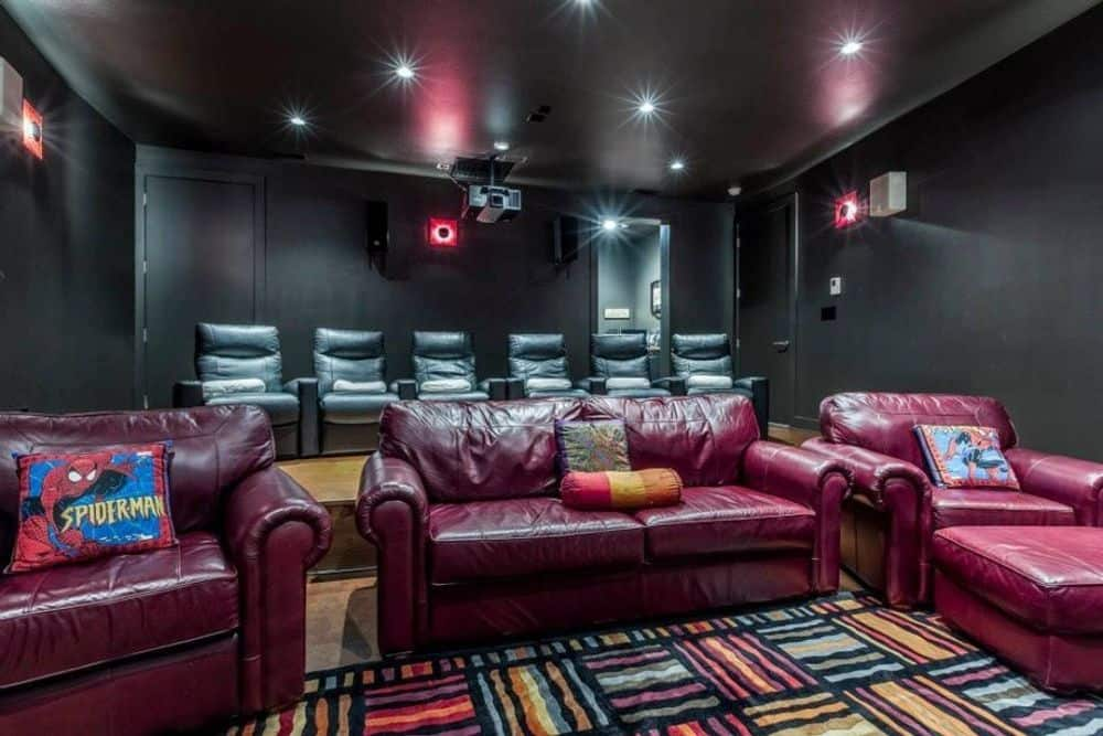Media room with black walls, leather seats, and a patterned area rug.