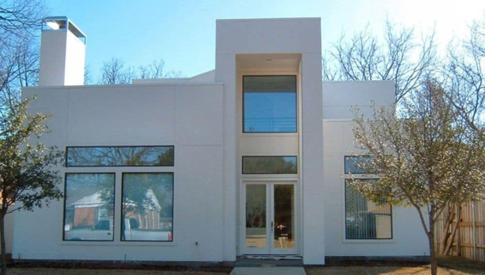 Front exterior view showing its clean lines, white exterior, and massive windows that flood the interior with natural light.