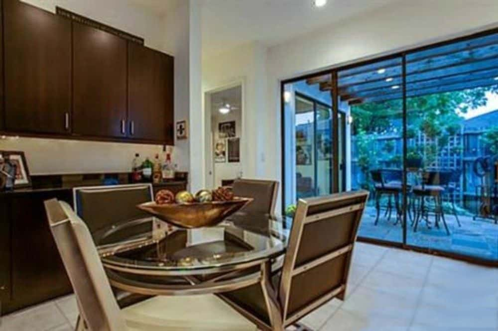Breakfast nook with built-in cabinets and a round dining set over tiled flooring.