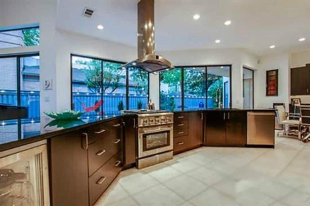 The kitchen offers dark wood cabinets and a stainless steel range topped with a matching vent hood.