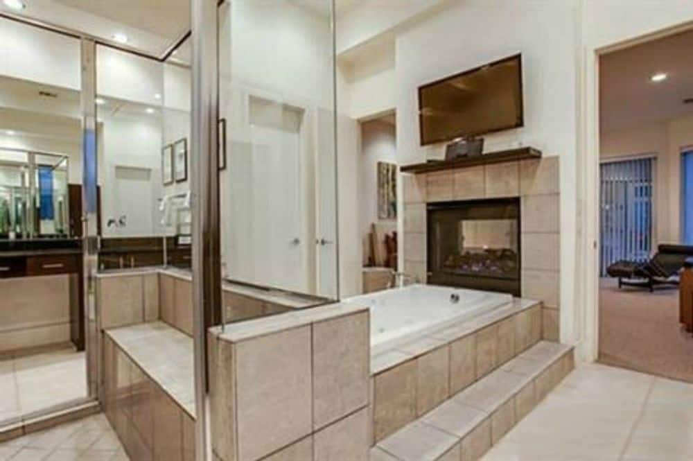The primary bathroom features a deep soaking tub topped with a double-sided fireplace and a wall-mounted TV.