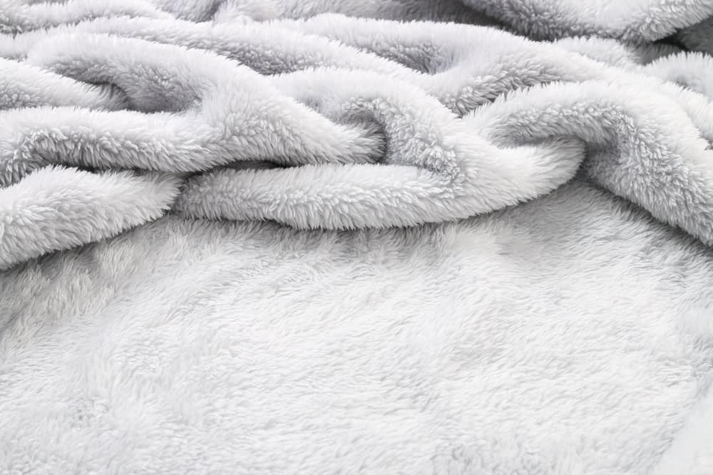 This is a white furry sou8ndproof blanket.