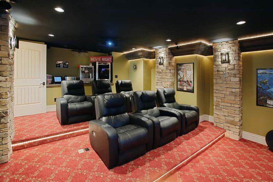 This is a close look at a home theater room with black leather theater chairs and soundproof carpeting.