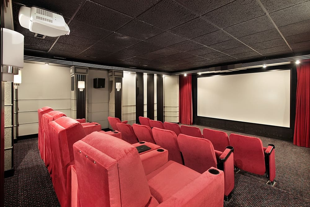 This is a close look at a home theater with red chairs and a dark gray carpeting to match the soundproof panels of the ceiling.