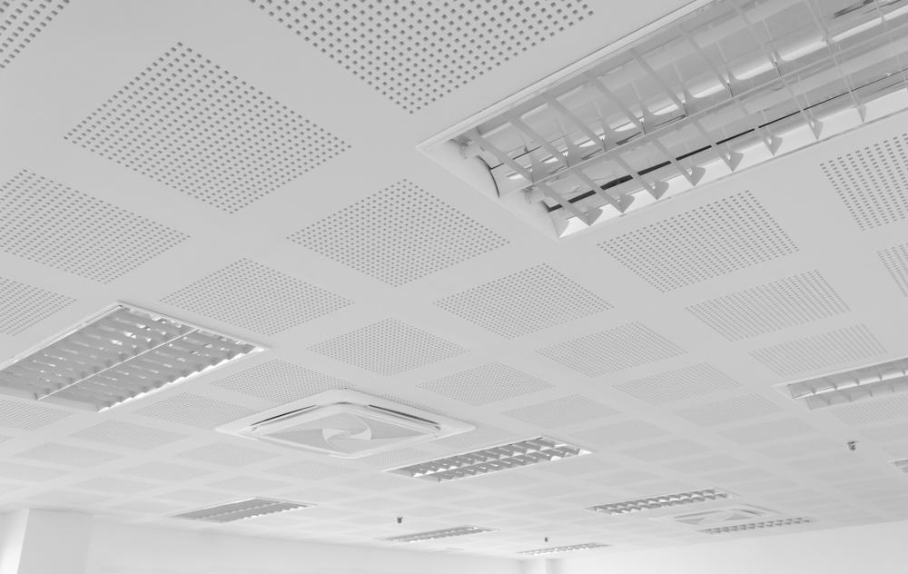 This is a close look at a bright ceiling with soundproof panel and modern lighting.
