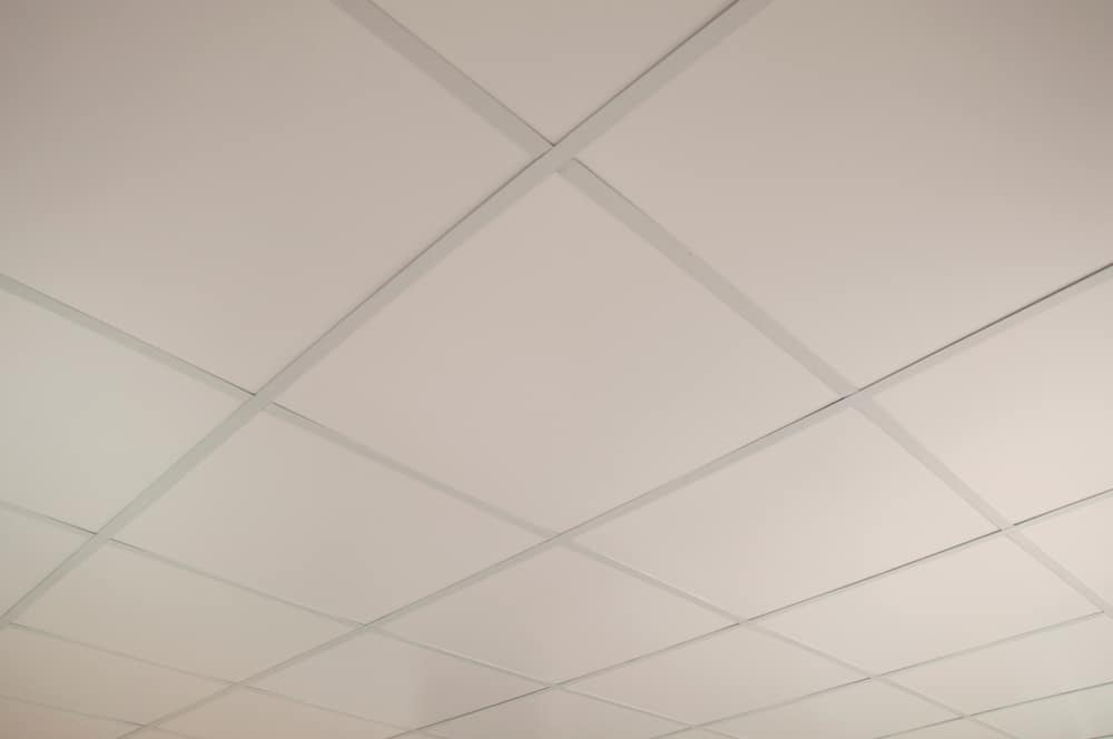 This is a close look at a high ceiling with beige soundproof panels.
