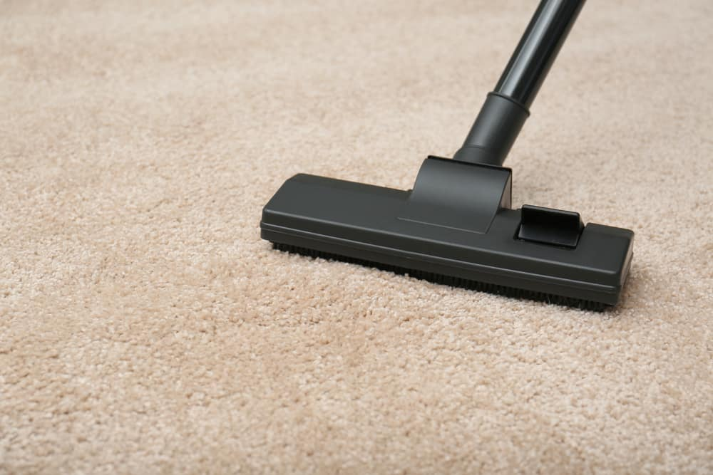 This is a close look at a soundproof beige carpeting on the floor being vacuumed.