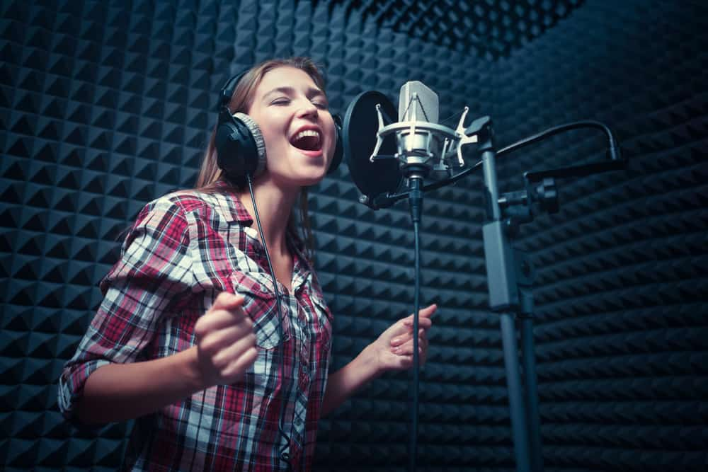 This is a close look at a woman singinside a recording studio with soundproofing.