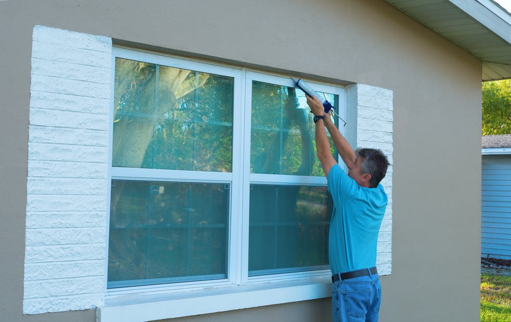 This is a close look of a man installing storm windows.