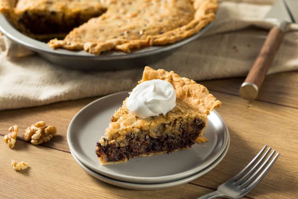 A slice of Kentucky Derby Pie with whipped cream topping.
