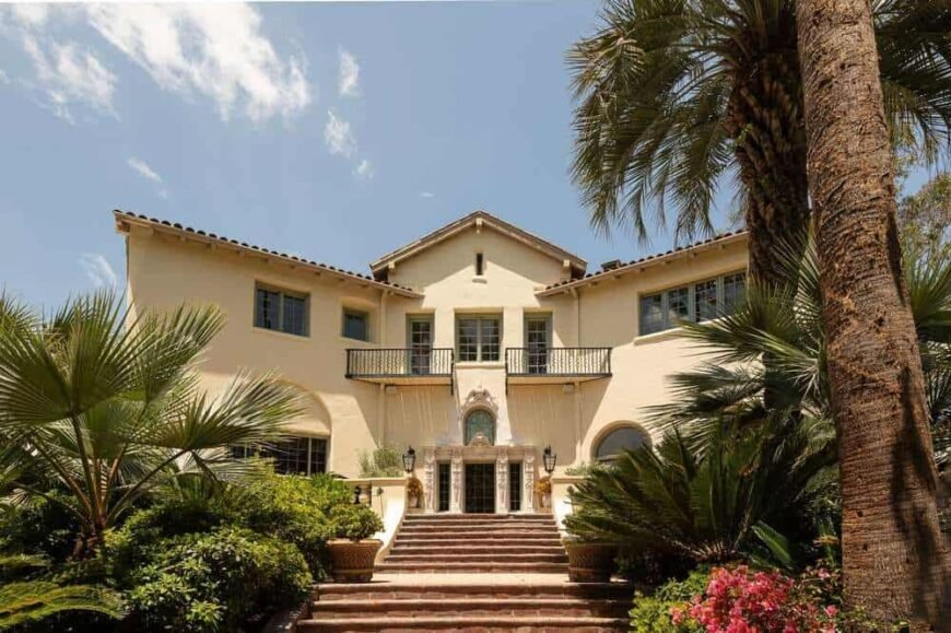 This is a front exterior view of the house with a set of outdoor steps flanked by tropical plants, trees and shrubs leading to the beige exteriors adorned with windows and a balcony. Image courtesy of Toptenrealestatedeals.com.