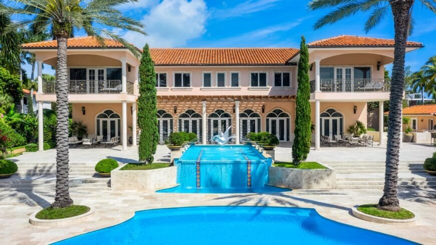 This is a full view of the back of the house with multiple arches, pillars and bright beige exterior walls adorned by the landscaping of trees, a water feature and a pool. Image courtesy of Compass.com.