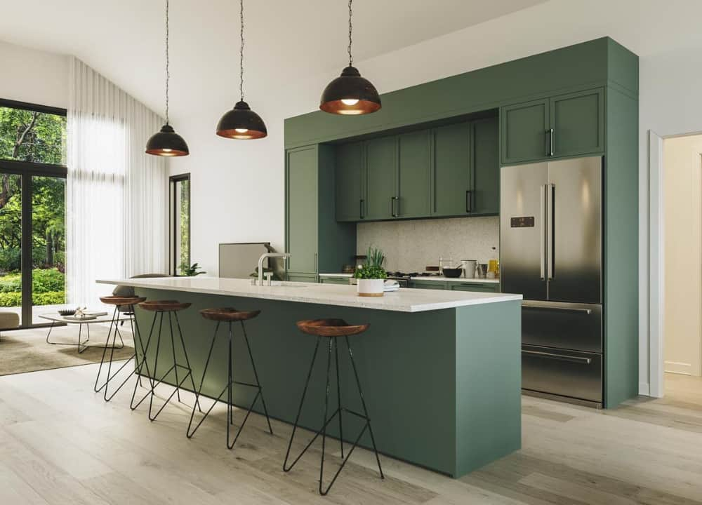 Kitchen with green cabinetry, stainless steel appliances, and a breakfast island paired with round bar stools.