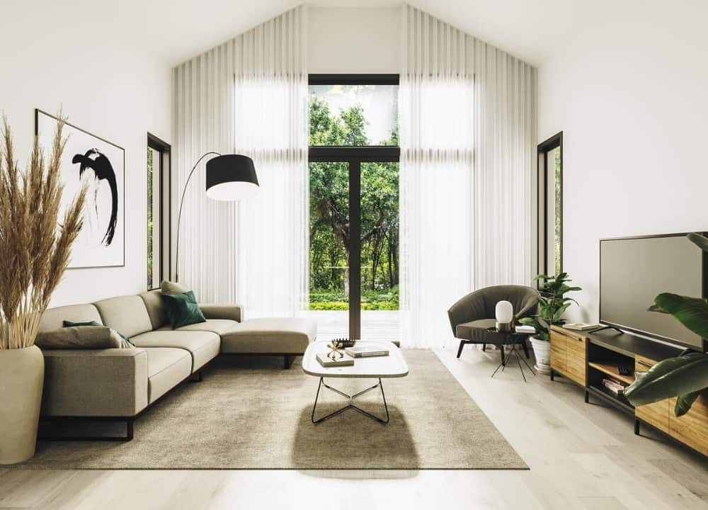 Living room with an L-shaped sectional, a metal coffee table, a TV, and large windows dressed in sheer curtains.
