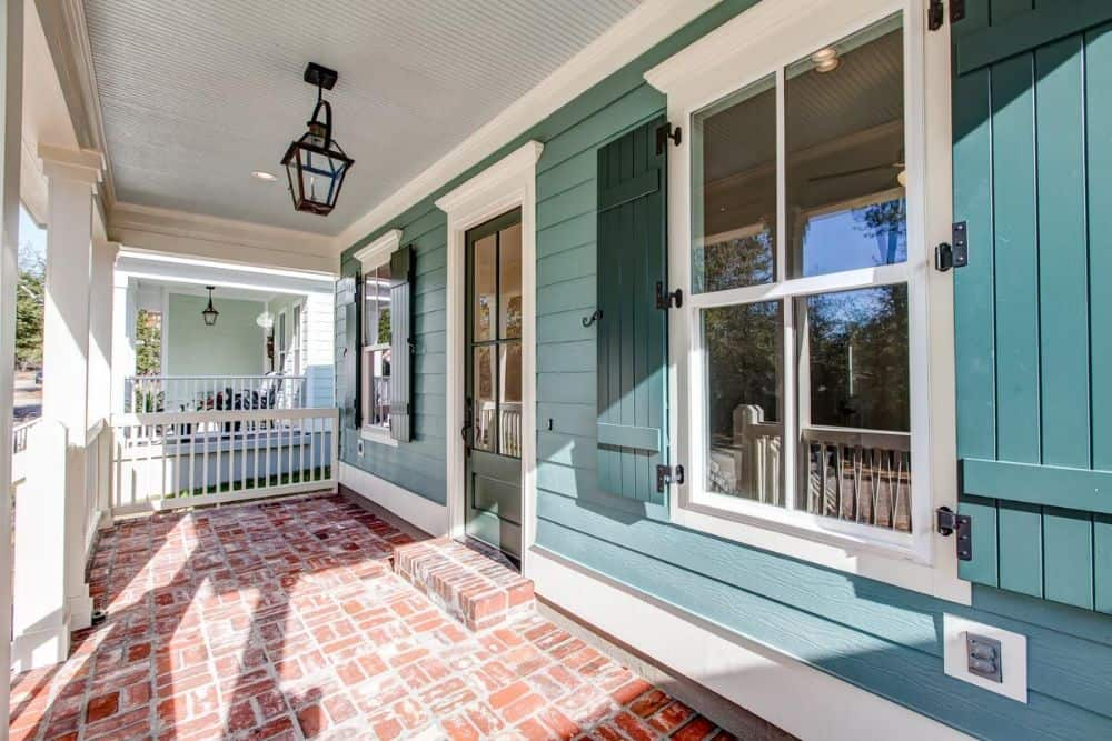 Entry porch with white railings, brick flooring, and a glazed front door.