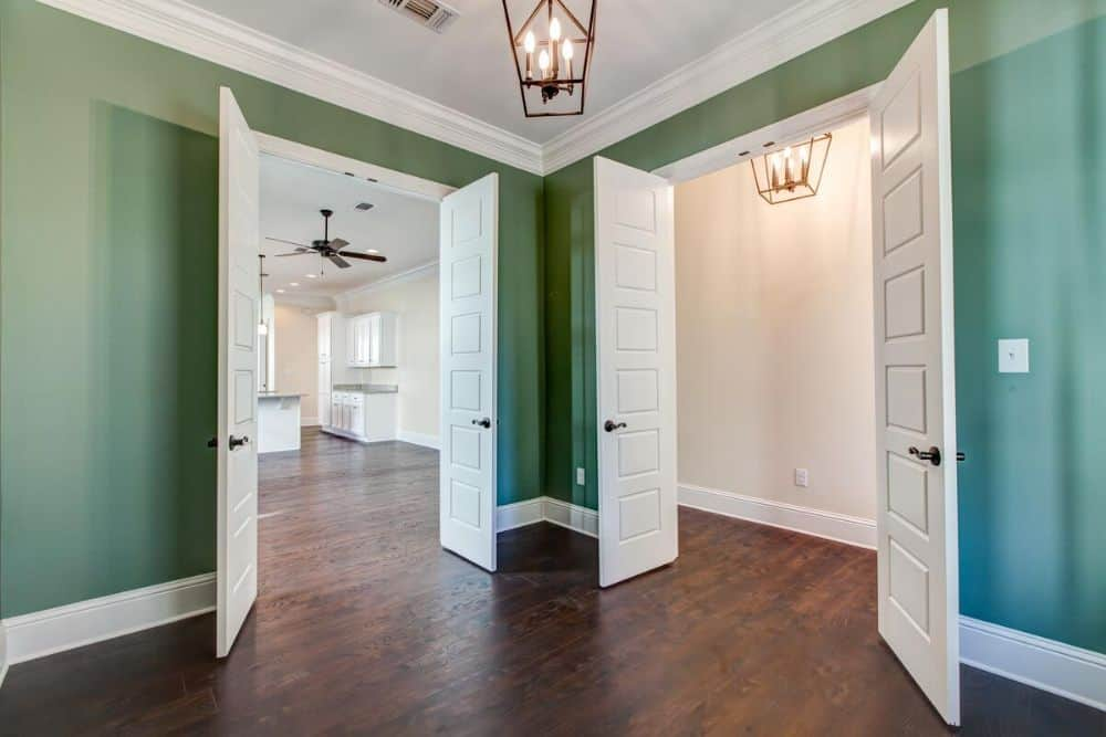 Flex room with green walls and two sets of white double doors leading to the living space.