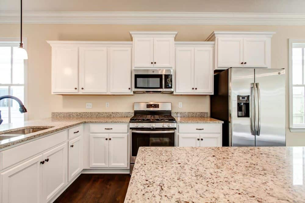 The kitchen is equipped with stainless steel appliances, white cabinetry, granite countertops, and a double bowl sink.