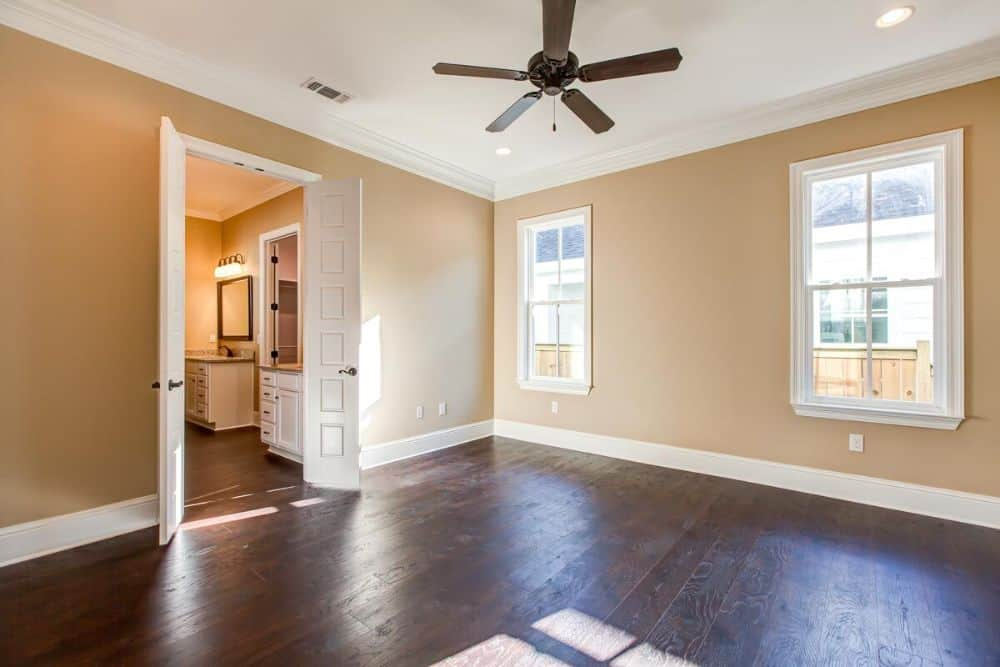 Primary bedroom with beige walls, a ceiling fan, and an ensuite resting behind the double doors.