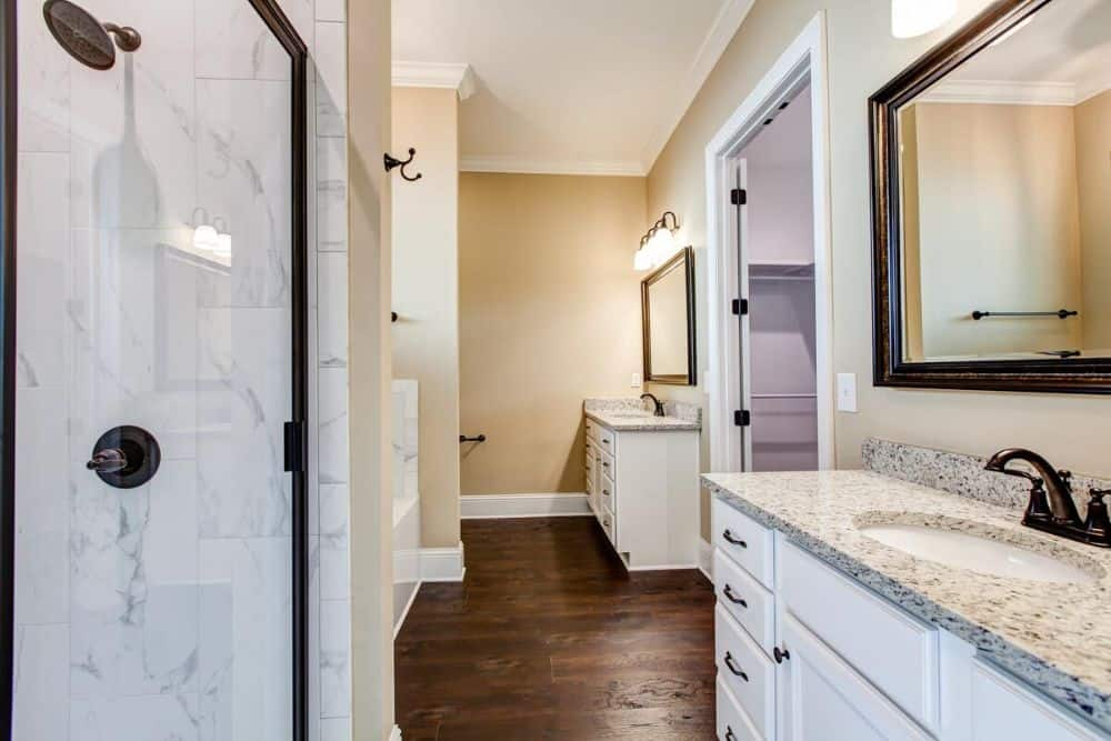 The primary bathroom includes his and her sink vanities along with a walk-in closet.
