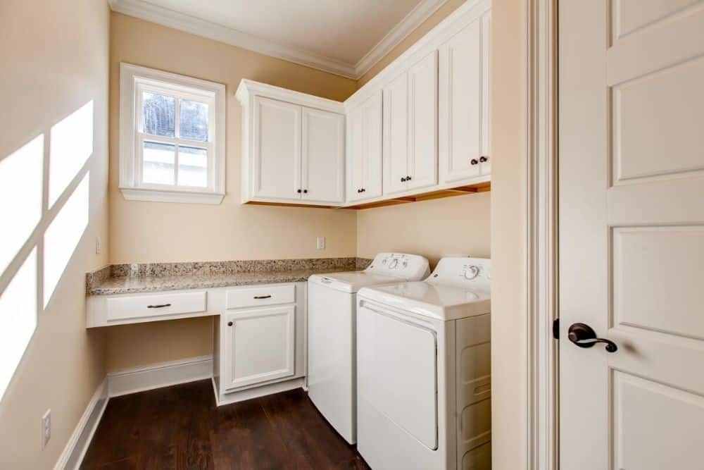 Laundry room with top load washer and dryer, white cabinets, a granite countertop, and a small window bringing natural light in.