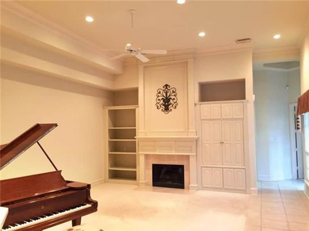 Family room with a baby grand piano and a fireplace flanked by white built-ins.