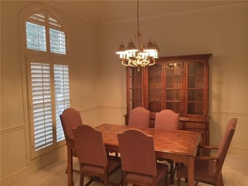 The formal dining room offers a louvered window, a china cabinet, and a 6-seater dining set illuminated by a classic chandelier.