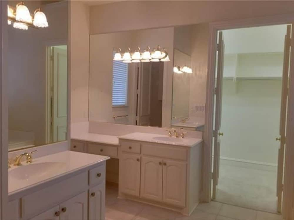 The primary bathroom is equipped with his and her sink vanities and a walk-in closet.