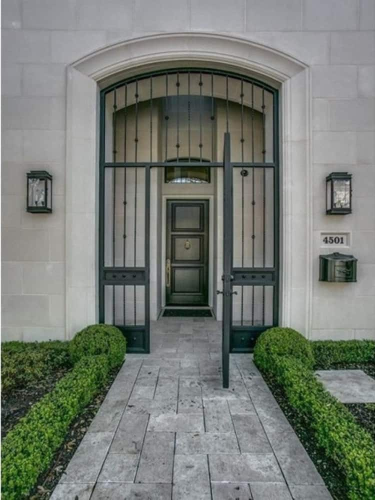 Main entrance with an archway, a wrought iron gate, and a dark wood front door.