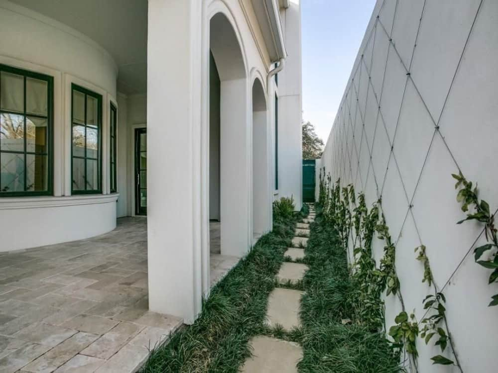 Concrete steps bordered by lush grass lead to the covered veranda.