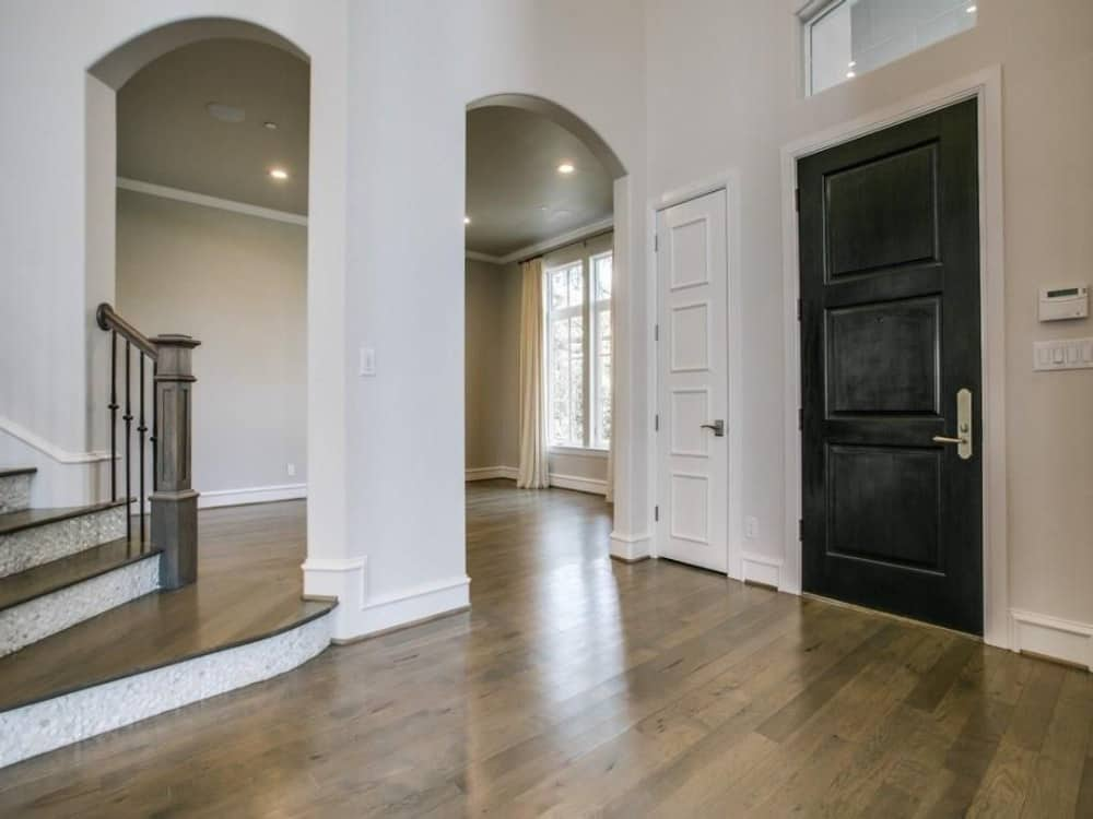 Foyer with hardwood flooring and storage closet concealed behind the white door. Open arches on the side lead to the formal dining room.
