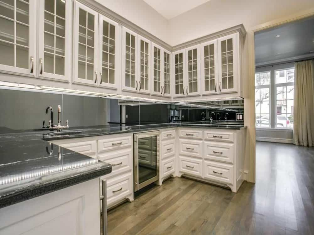 The butlery is equipped with glass front cabinets, a wine fridge, and a small sink.