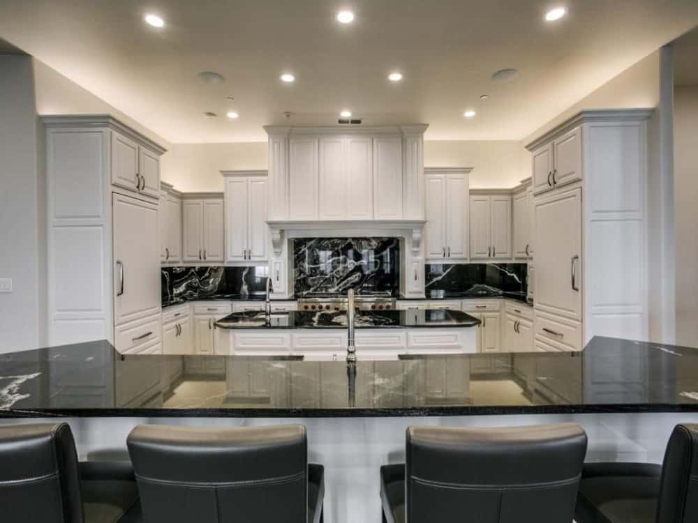 Kitchen with white cabinetry, black marble countertops, a center island, and an eating bar fitted with a sink.