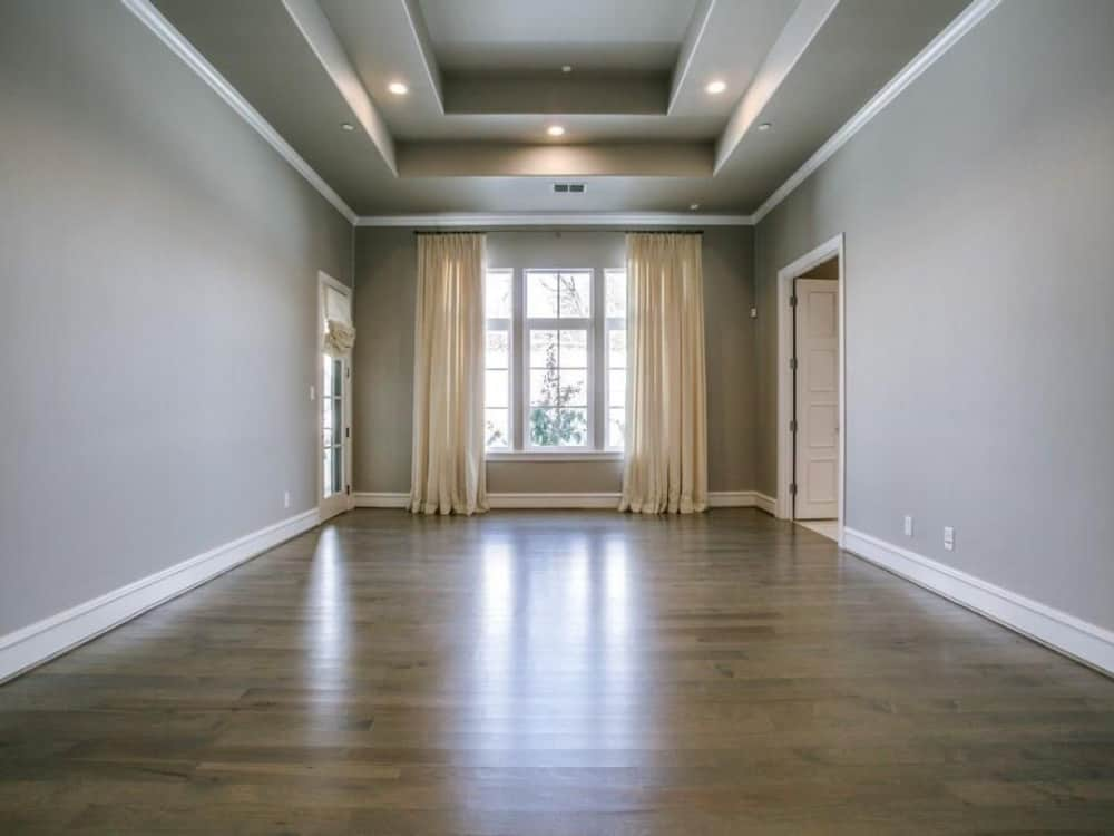 The primary bedroom features a stunning step ceiling, gray walls, and a trio of windows dressed in cream drapes.