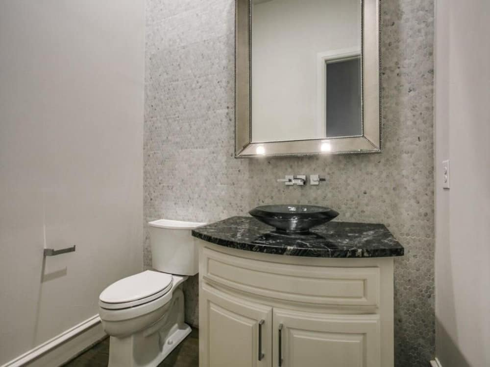 Powder room with a toilet and a vessel sink vanity paired with a chrome framed mirror.