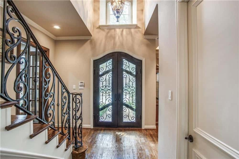Foyer with a french entry door, a staircase, and an ornate pendant hanging from the high ceiling.