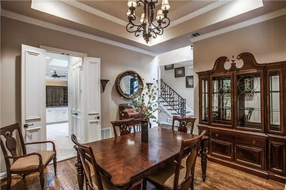 Dining room with wooden dining set, a matching china cabinet, and a wrought iron chandelier mounted on the tray ceiling.