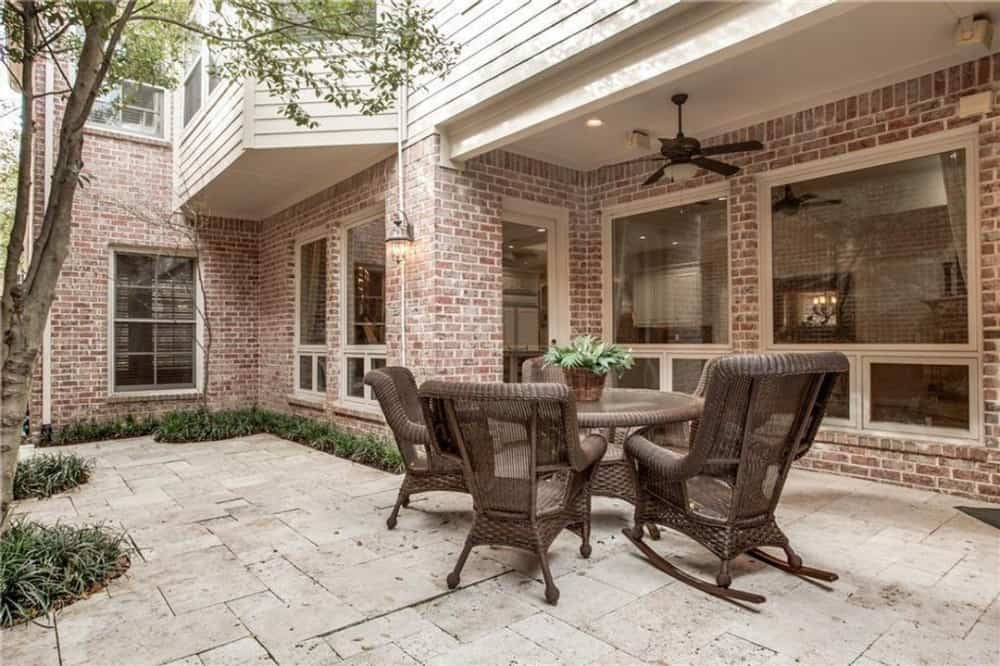 Open patio with wicker armchairs and a matching round table over limestone flooring.