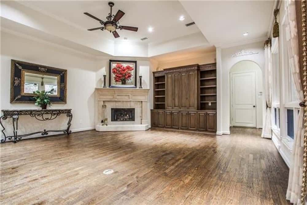 Family room with a corner fireplace, a wooden cabinet, and a metal console table paired with a decorative mirror.