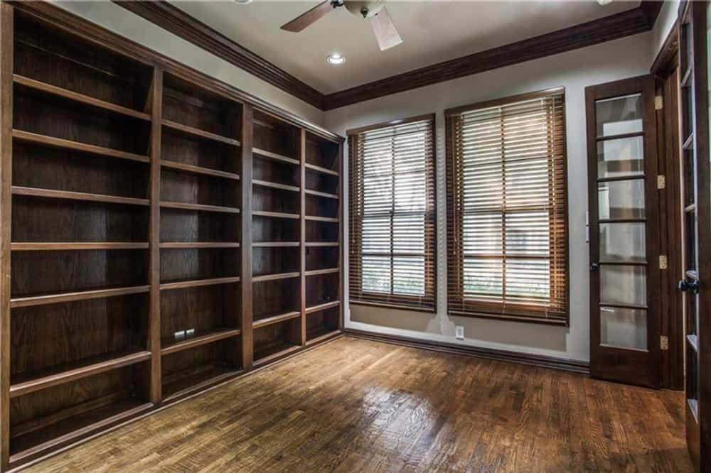 Heavy wooden elements run throughout the study. There are also framed windows bringing natural light in.