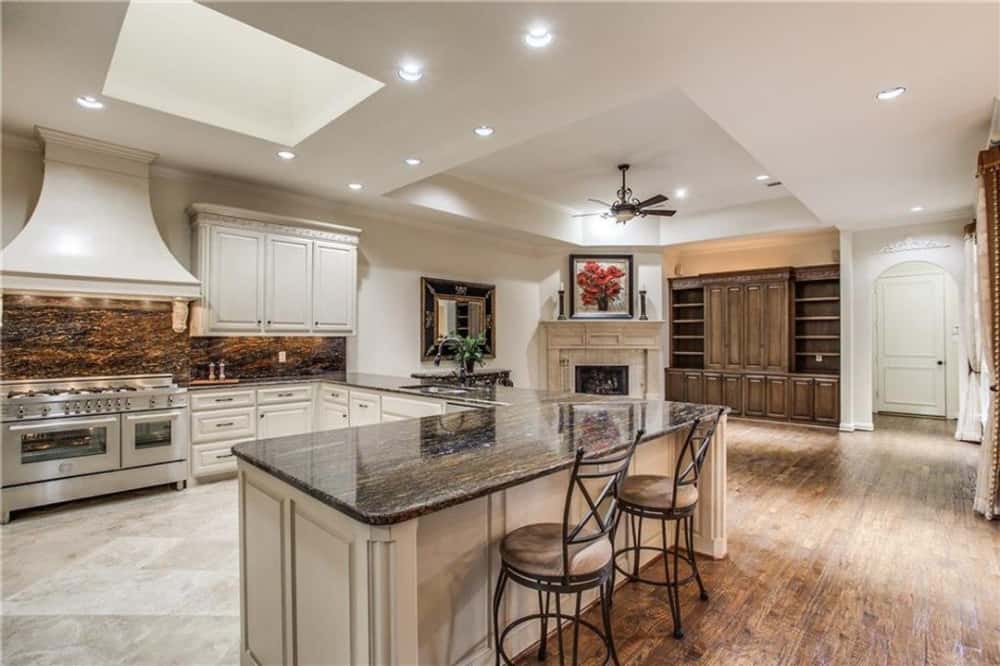 The kitchen has white cabinetry, a breakfast bar, and a skylight.