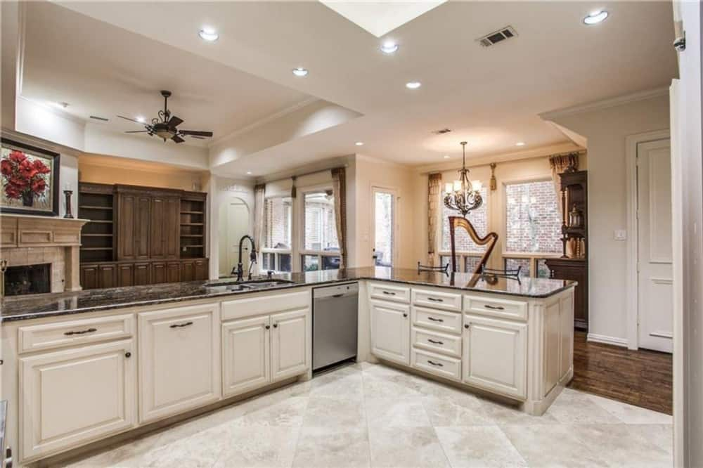A beige velvet rug defines the kitchen from the open living space.
