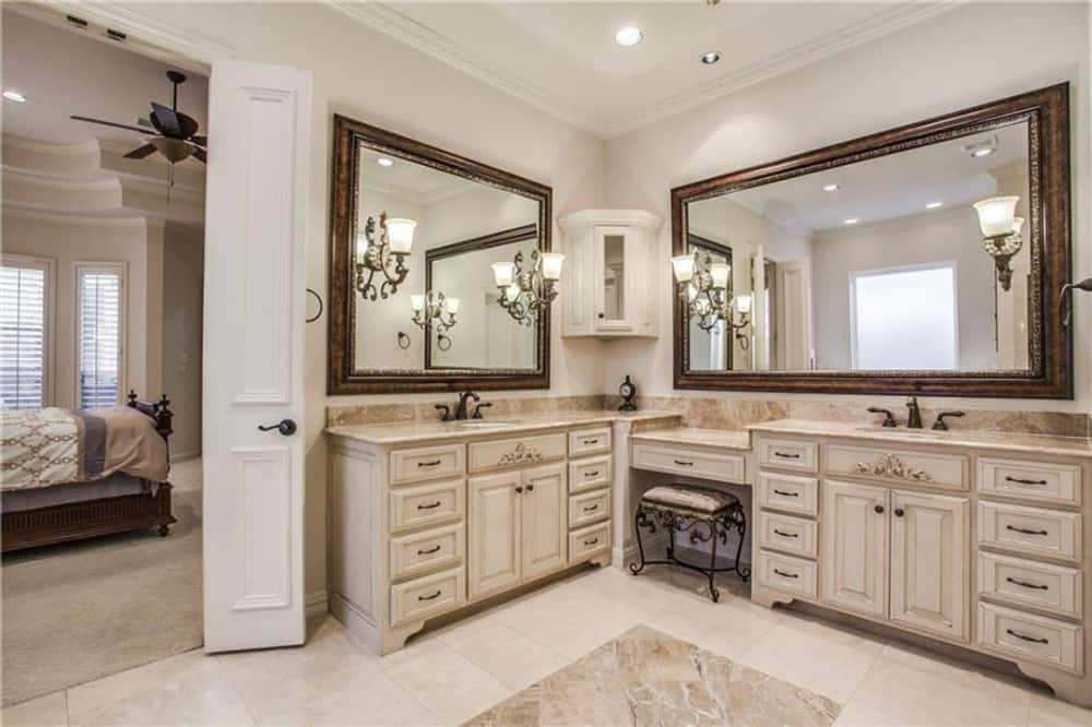 The primary bathroom features his and her sink vanities with a makeup counter paired with an ornate stool.