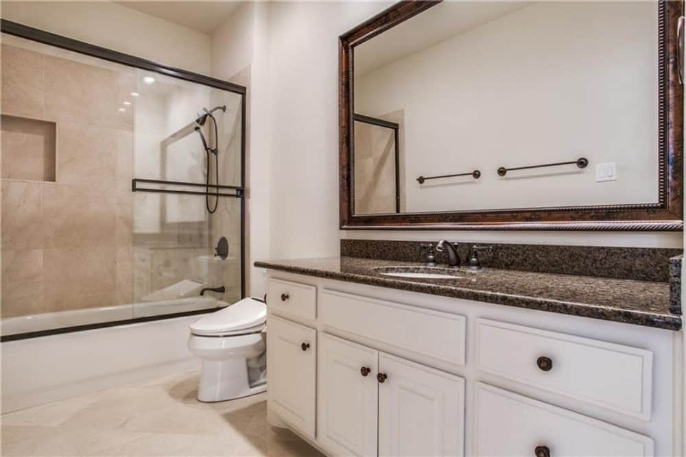 This bathroom is equipped with a sink vanity, a toilet, and a tub and shower combo.