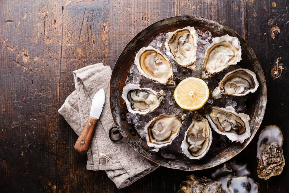 This is a bunch of open oysters on ice with a slice of lemon.