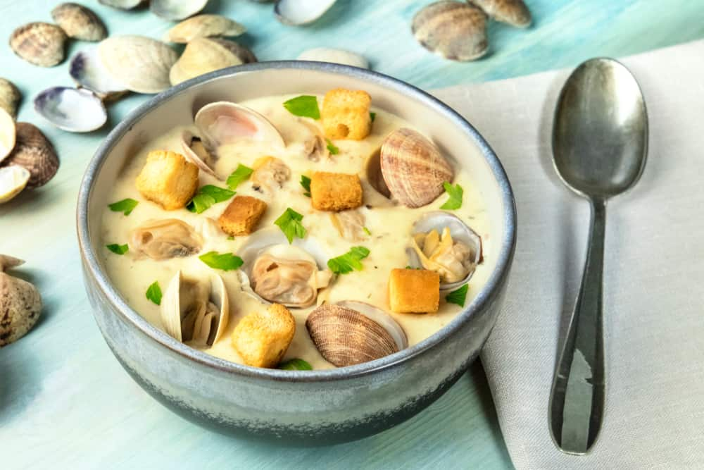 This is a bowl of clam chowder with parsley and croutons.